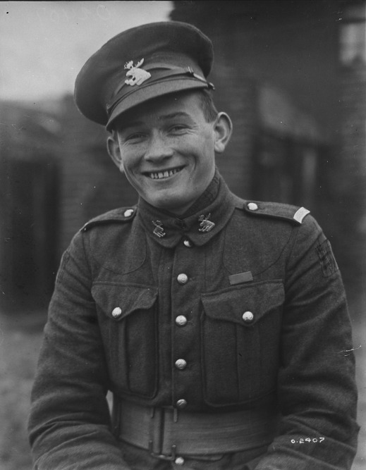 A black-and-white photograph of a smiling young man in uniform with his cap slightly askew.