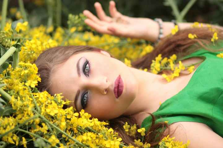 close up portrait of young woman with yellow flowers