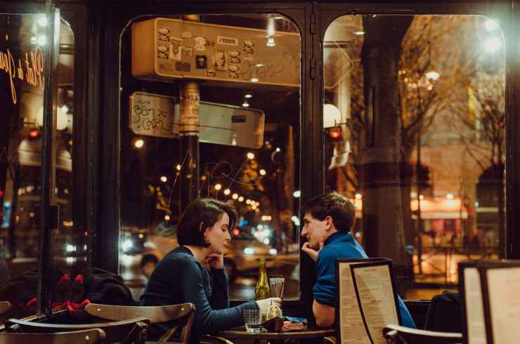 selective focus photography of man and woman sitting on chair inside restaurant during nighttime