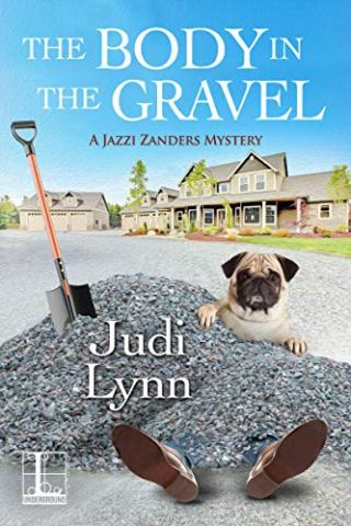 Book cover for The Body in the Gravel by Judi Lynn shows a pile of gravel with feet sticking from the bottom, shovel stuck in gravel near top, cut pug dog looking over the pile, and a house in the brackground
